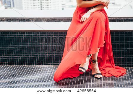 Fashionable Woman Sitting Crossed Legs In Long Red Dress