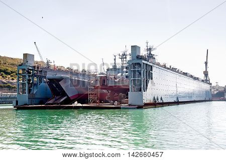 Floating dry dock with two landing crafts under repair inside.