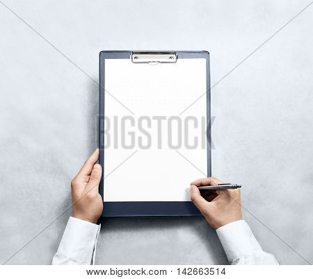 Hand signing blank clipboard with white a4 paper design mockup. Clear document holder mock up template hold arm. Clip board notepad surface display front. Checklist tablet plan file presentation.