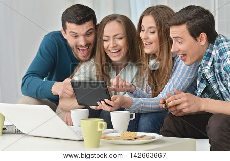 portrait of happy friends and  laptop and tablet pc at home