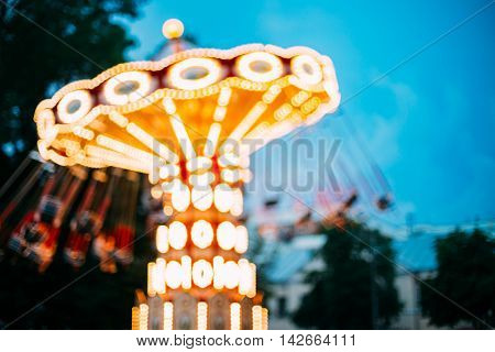 Abstract Motion Blurred Image Of Brightly Color Illuminated Dynamic Rotating Carousel Merry-Go-Round In Amusement City Park On Blue Evening Sky Boke Bokeh Background.