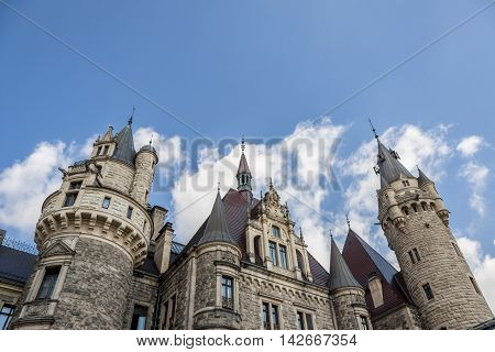 MOSZNA POLAND - AUGUST 7: Part of the Moszna Castle is a historic castle located in a small village on august 7 2016 in Moszna. The castle is one of the best known monuments in Upper Silesia.