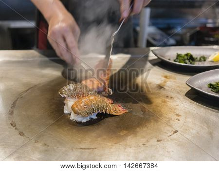 Japanese teppanyaki with lobster tail on hot plate