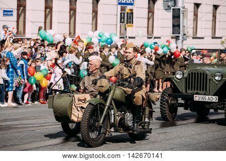Gomel, Belarus - May 9, 2016: The Moving Tricycle Sidecar With Two Men In Soldiers Uniform And Machine Gun Of WW2 Time On Board. A Part Of Demo Parade Procession On Victory Day 9 May.