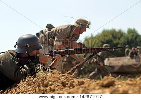 WESTERNHANGER, UK - JULY 18: WW2 German army reenactors participate in an allis vs axis battle reconstruction at the War and Peace show on July 18, 2014 in Westernhanger
