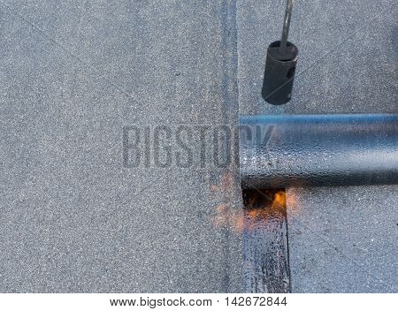 Roofer man worker at building site installing roll of roofing felt with gas blowpipe torch during construction works. flame during welding of a waterproofing membrane on a roof