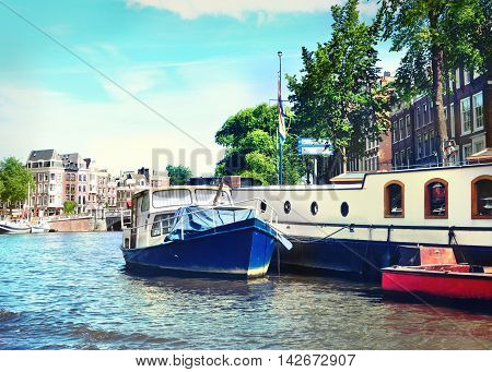 Canal at Amsterdam city, Amstel river with houseboat.