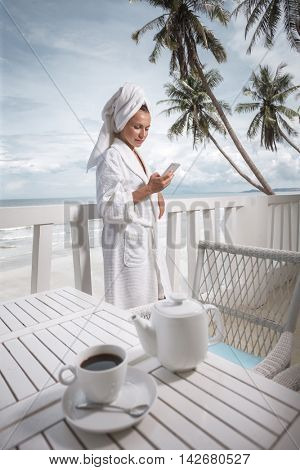 Woman with coffee and mobilephone in hotel terrace over sea view