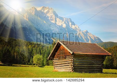 Sunrise over Zugspitze. It is Germany's highest peak (2962 m). View from a Garmisch Partenkirchen valey. Old hayloft in mountain landscape, Bavaria, Germany. Warm filtered picture.