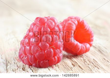Two red ripe raspberries on wooden background