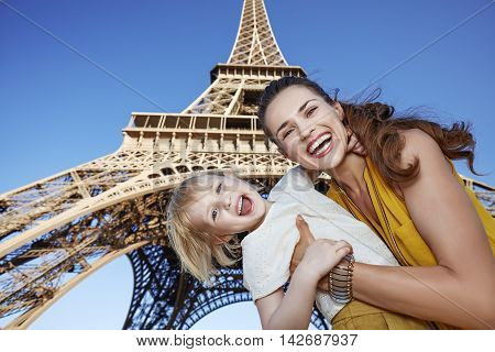 Cheerful Mother And Daughter Travellers Against Eiffel Tower