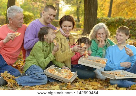 Happy smiling family eating pizza in autumn park