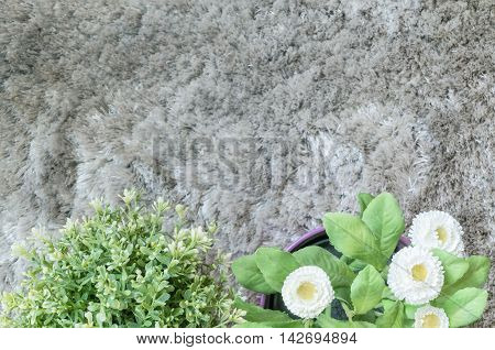Closeup artificial plant with white flower in pot on blurred gray carpet textured background in top view