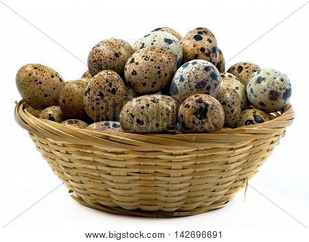 Wooden basket with the quail eggs isolated on white background