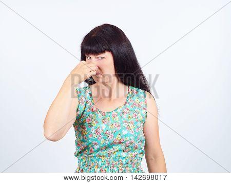 женщина зажимает нос пальцами рук