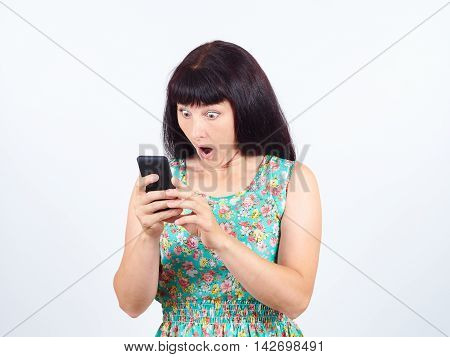 A young woman reads the SMS the news on the phone. Emotions body language facial expression. poster