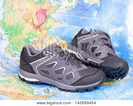 Walking trekking shoes on the world map. Travel and tourism.