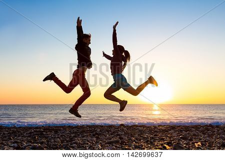 Silhouettes of Girl and Guy jumping high with arms up spectacular Sunrise at Ocean coast Pebble Beach reflection at Surf blue Sky