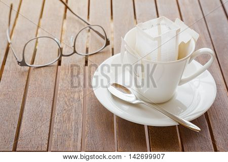 White coffee cup and spoon with white pre-packaged blended coffee in paper filter set on wooded table with out of focus blurred eyeglasses in background
