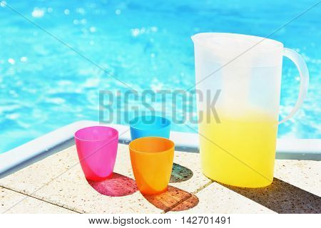 Drink in a teapot with cups at the pool. Drinking water in the hot summer.