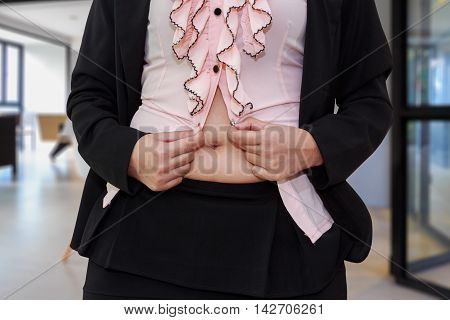 Chubby businesswoman cannot button up her clothes in room. belly fat concept