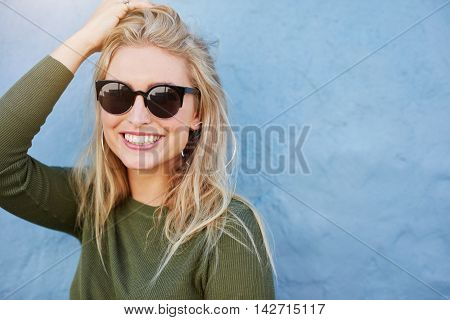 Close up shot of pretty young woman in sunglasses smiling. Attractive young female model with copy space on blue background.