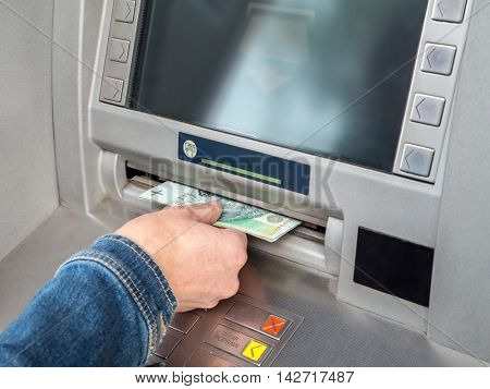 Closeup of woman's hand withdrawing cash from ATM slot