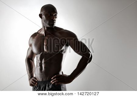 Shirtless Male Model Posing Against Grey Background