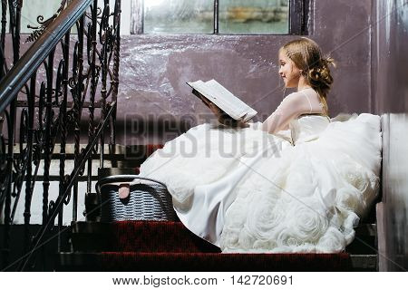 small girl kid with long blonde hair and pretty happy smiling face in prom princess white dress with basket sitting near building glass big window on stairs reading book