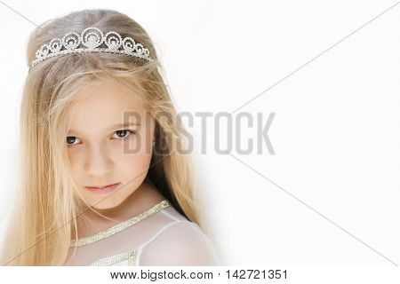 small girl kid with long blonde hair and pretty face in dress and prom princess crown standing on white background closeup