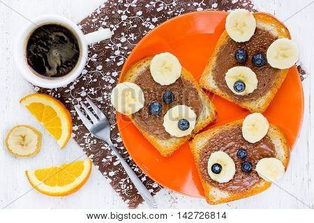 Cute bear toast with chocolate banana and blueberry - creative food art idea for kids breakfast top view