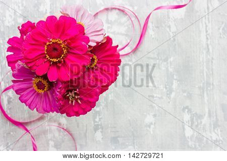 Pink flowers on gray white shabby chic background. Festive greeting card top view empty space for text