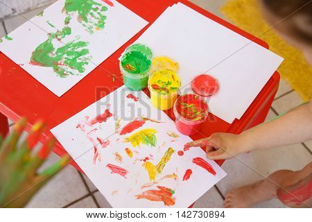 Children painting a drawing with finger paints used for finger drawing and sensory play. Fun childhood sensory and experience-based learning concept.