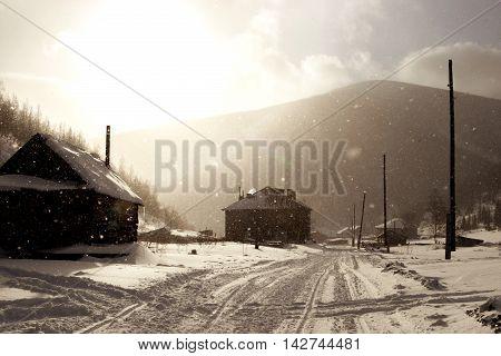 Snowy misty village street in Siberia in winter