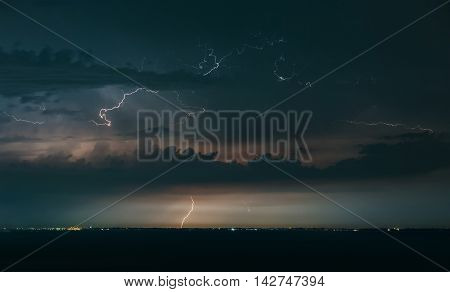 Massive drammatic cloud to ground lightning bolts hitting the horizon of city lights