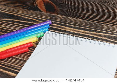 Copyspace Blank Sheet of White Paper with Multiple Colorful Felt Pen Markers on Wooden Background.