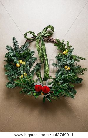 Christmas floral wreath decoration with baubles, red bow, holly and winter greenery over kraft background