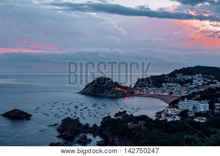 Buch sea with boats the famous Village of Tossa de Mar on the Costa Brava at Night, Catalonia, Spain.
