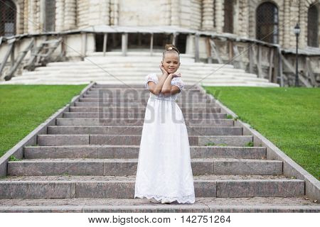 Portrait of a beautiful young little girl in white gown, summer outdoors