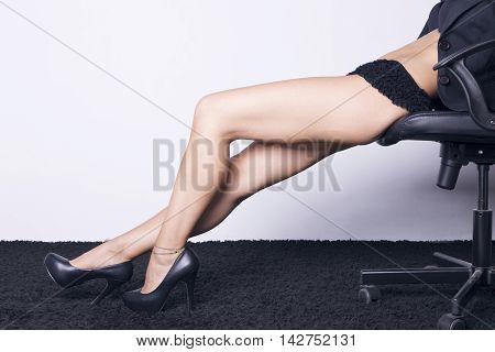 Business woman seated on a chair showing her sexy legs with lingerie and heel shoes over a white background.