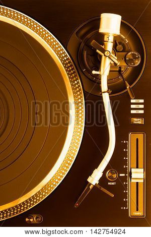 part of dj turntable with tonearm, top view, golden tone