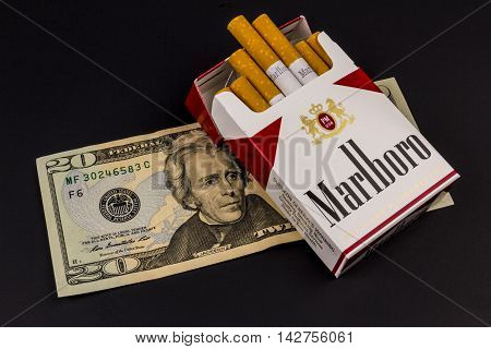 Indianapolis - Circa August 2016: Marlboro Cigarettes and Twenty Dollar Bills Representing the High Costs of Smoking. Marlboro is a product of the Altria Group V
