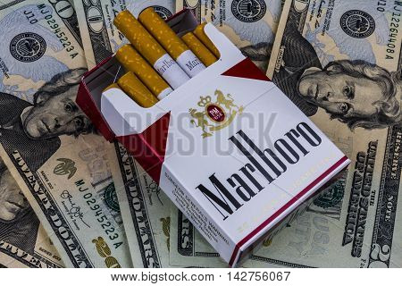 Indianapolis - Circa August 2016: Pack of Marlboro Cigarettes and Twenty Dollar Bills Representing the High Costs of Smoking. Marlboro is a product of the Altria Group IV