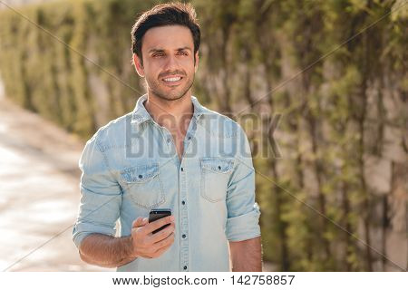 Outdoor Portrait Of Modern Young Man With Mobile Phone In The Street