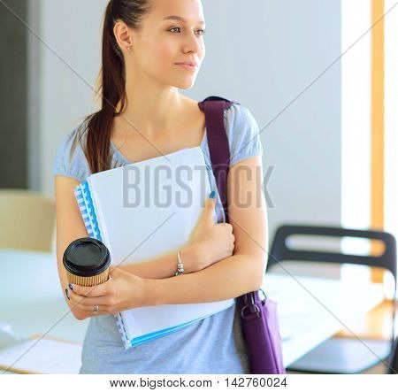 Smiling student with folders and cup of coffee
