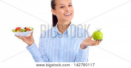 Portrait of a beautiful woman doctor holding a plate with fresh vegetables and green apple