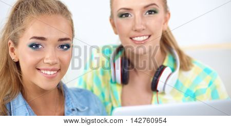 Two young women sitting with laptop