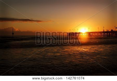 the sun rises above a pier on the Atlantic Ocean