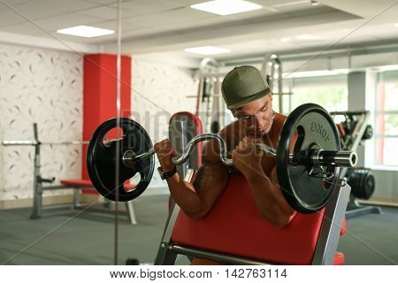 Sport time. Shirtless bodybuilder exercising with barbell