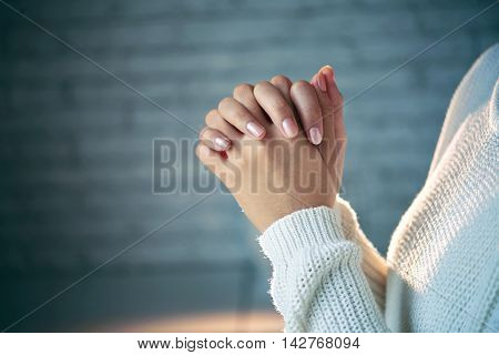 Hands of woman making a wish, side view